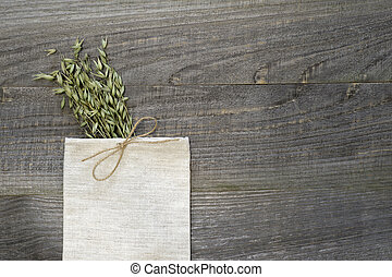Small linen bag knotted with jute twine with green ears of oats on a wooden volumetric background.
