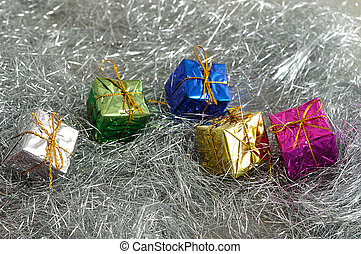 Small little gifts wrap in Shiny paper placed on Silver tinsel