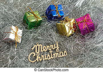 Small little gifts wrap in Shiny paper with merry Christmas placed on Silver tinsel