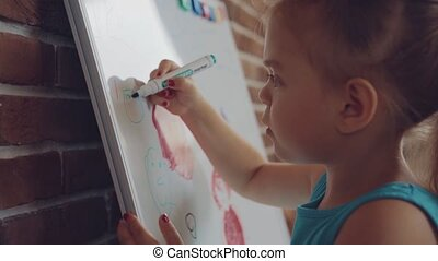 Small little girl draws picture on whiteboard - Small little...