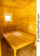 small log cabin interior with bed and window