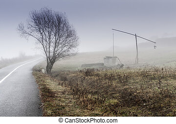 Small lonely provincial farm with weel pole weel on a foggy...