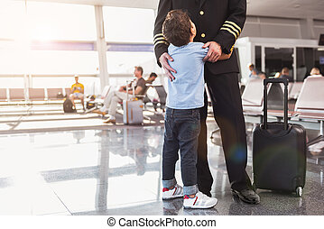 Small male person hugging father aviator - Little son is ...