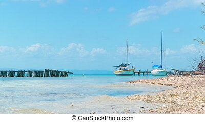 Small Marina at Coral Island - Two boats slowly swinging on...