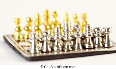 Small metalic chess figures in start position spin isolated ...