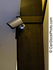 Small modern CCTV is installed on the wooden pillar.