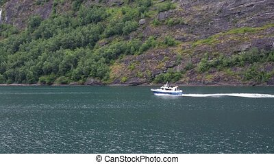 Small motor boat with tourists in Norway fjord - Small motor...
