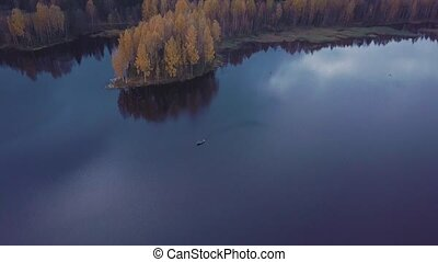 Small motorboat floats on rippling blue water of the lake...