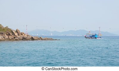 Small motorboat in the Nha Trang bay, Vietnam. Vinpearl cable car in the background. View from a moving boat.