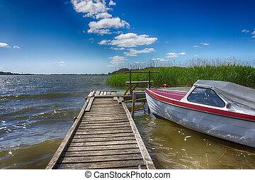 Small motorboat moored alongside a wooden jetty