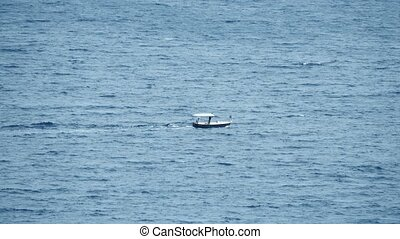 Small motorboat moving at sea - Distant small motorboat...