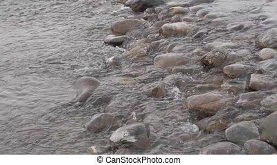 small mountain creek in winter season. Gurgling water stream...