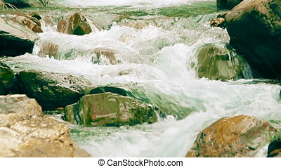 Small mountain river with artificial rapids made of cobblestones. Slow zoom out effect.