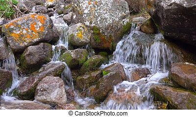 Small mountainous waterfall among lichen covered rocks. 4K...