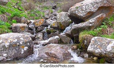 Small mountainous waterfall among lichen covered rocks. 4K...