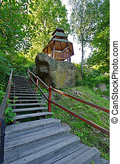 small narrow stairs leading to a gazebo surrounded by tall trees
