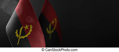 Small national flags of the Angola on a dark background