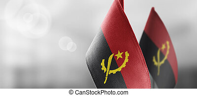 Small national flags of the Angola on a light blurry background