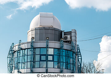 small observatory and planetarium over a blue cloudy sky