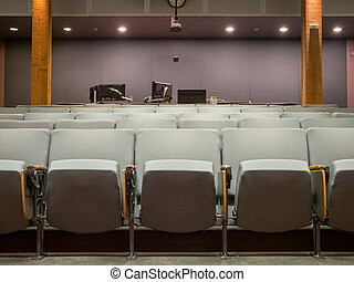 Small office auditorium with gray chairs and computer monitor set up in rear
