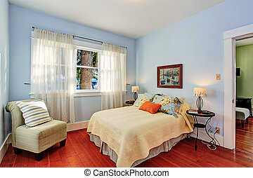 Light blue bedroom with window and hardwood floor furnished with bed and chair