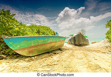 Small old fishing boat on a Maldivian beach