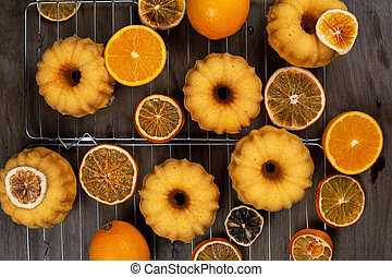 Small orange bundt cakes with fresh and dry oranges on...