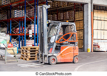 Small orange forklift parked at a warehouse