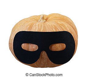 Small orange pumpkin in masquerade mask