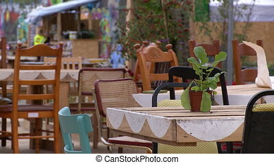Static view of small, outdoor restaurant, with tables crafted from pallets and surrounded by plants and vegetation, and accompanied by people