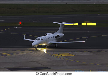 small passenger jet airplain at an airport in the evening