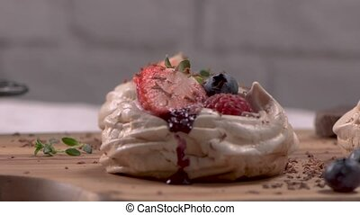Small pavlova cakes with fresh Strawberries and blueberries.