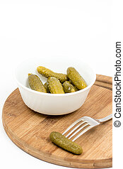 Small pickles in the white bowl and pickle on the fork