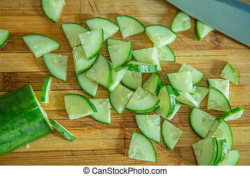 Small pieces of cucumber for salad on a wooden cutting board and cook knife