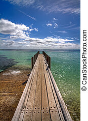 view of a small boat pier reaching out into the crystal clear waters at Augusta, Margaret River, Australia