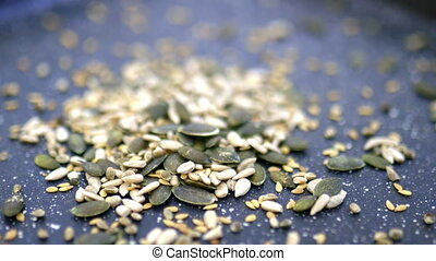 Sunflower seeds, linseed, and lentils dropping on black tray. Pile of fresh seeds on metal tray up-close. Healthy snacks