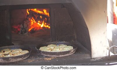 small pizza baking in the oven burning fire. slow motion lifestyle video. the cook prepares pastries on an open fire. baking in the oven with fire concept cooking