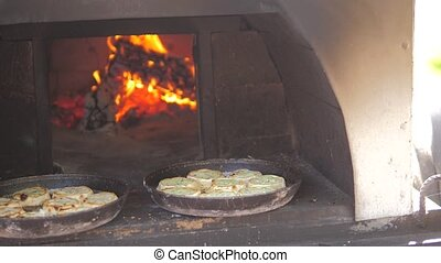 small pizza baking in the oven burning fire. slow motion video lifestyle. the cook prepares pastries on an open fire. baking in the oven with fire concept cooking