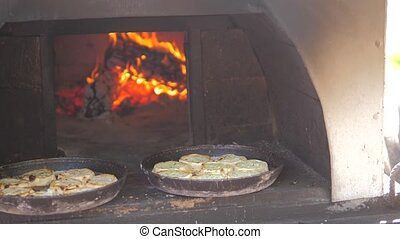 small pizza baking in the oven burning fire. slow motion...
