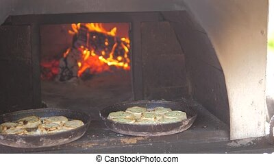 small pizza baking in the oven burning fire. slow motion video. the cook lifestyle prepares pastries on an open fire. baking in the oven with fire concept cooking