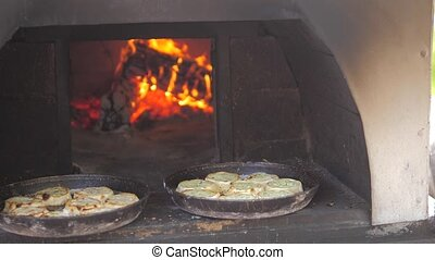 small pizza baking in the oven burning fire. slow motion video. the cook prepares lifestyle pastries on an open fire. baking in the oven with fire concept cooking