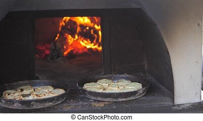 small pizza baking in the oven burning fire. slow motion video. the cook prepares pastries lifestyle on an open fire. baking in the oven with fire concept cooking