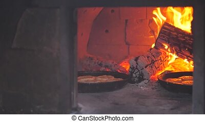 small pizza baking in the oven burning fire. slow motion video. the cook prepares pastries on an open fire. baking in the oven with fire concept lifestyle cooking