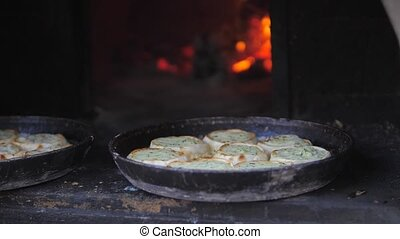 small pizza baking in the oven burning fire. slow motion video. the cook prepares pastries on an open fire lifestyle. baking in the oven with fire concept cooking