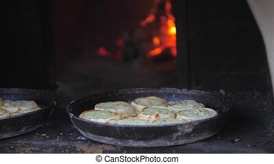 small pizza baking in the oven burning fire. slow motion video. the cook prepares pastries on an lifestyle open fire. baking in the oven with fire concept cooking