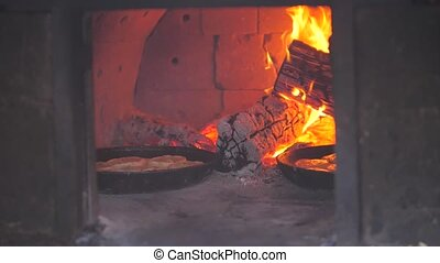small pizza baking in the oven burning fire. slow motion video. the cook prepares pastries on an open fire. baking in the oven with fire lifestyle concept cooking