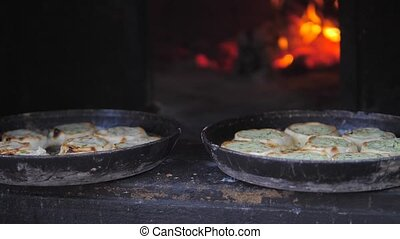 small pizza baking in the oven burning fire. slow motion video. the cook prepares pastries on an open fire. lifestyle baking in the oven with fire concept cooking
