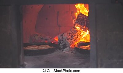 small pizza baking in the oven burning fire. slow motion video. the cook prepares pastries on an open fire. baking in the oven with lifestyle fire concept cooking