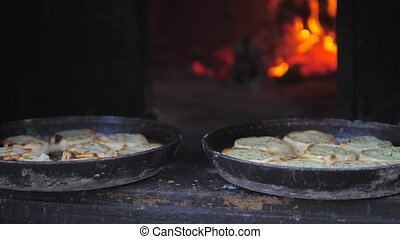 small pizza baking in the oven burning fire. slow motion video. the cook prepares pastries on an open lifestyle fire. baking in the oven with fire concept cooking