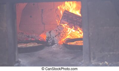 small pizza baking in the oven burning fire. slow motion video. the cook prepares pastries on an open fire. baking in the oven with fire concept cooking lifestyle
